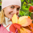 Attractive young girl with a bunch of autumn leaves — Stock Photo