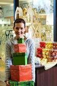 Teenager girl with gift boxes in a shop — Stockfoto