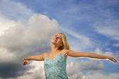 Beautiful blond girl with arms wide open over blue cloudy sky — Stockfoto