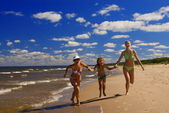 Mother and two daughters running on a beach near the water — Stock Photo