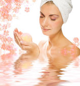 Beautiful young woman with aroma bath ball reflected in rendered — Stock Photo
