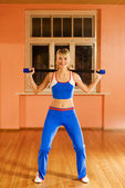 Attractive fitness trainer lifting a stick — Stock Photo