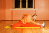 Fitness trainer showes stretching exersise — Stock Photo
