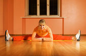 Beautiful fitness trainer does splits on a floor — Stock Photo