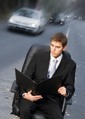 Handsome business man on sitting in executive chair on a road — Stock Photo