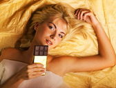 Beautiful girl with a chocolate craving lying on luxury golden f — Stock Photo