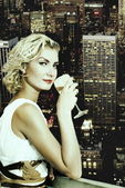 Beautiful blond girl drinks champagne on a skyscraper in megapol — Stock Photo