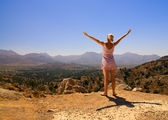 Beautiful girl standing on a mountain with her hands wide open — Stock Photo