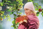 Schönes mädchen mit herbstlaub nahe dem apfelbaum und blau f — Stockfoto
