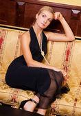 Sexy blond girl sitting on a luxury sofa — Stock Photo