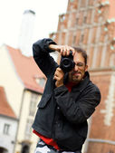 Handsome guy with a digital camera (shallow DoF) — Stockfoto