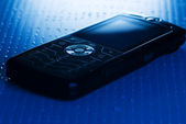 Blue toned picture of a mobile phone (shallow DoF, focused on ro — Stock Photo