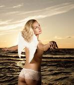 Sepia toned photo d'un bel ange dans une mer au moment du coucher du soleil — Photo