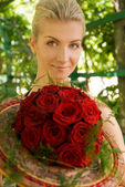 Beautiful girl with a bouquet of red roses — Stock Photo