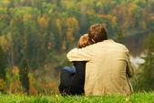 сладкая парочка сидит на холме и, глядя на осенние пейзажи — Стоковое фото