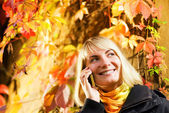 Happy girl talks to on the phone, autumn background behind her — Stockfoto