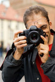 Handsome guy with a digital camera — Stock Photo