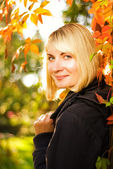 Beautiful smiling blond girl at sunny autumn day — Stock Photo