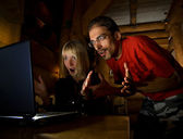 Two friends with surprised faces working on the computer — Stock Photo