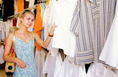 Blond girl buying clothes in a shop — Stock Photo