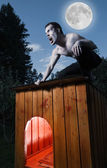 Scary man sitting on a doghouse and turning into werewolf — Stock Photo