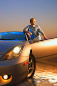 Handsome guy near the modern sport car at sunset time — Stock Photo