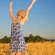 Beutiful blond girl jumping in the wheat field — Stock Photo