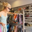 Blong girl buying clothes in a shop — Stockfoto