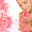 Beautiful girl with aroma bath ball in rendered water — Stock Photo
