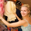 Young beautiful girl buying clothes in a shop — Стоковая фотография