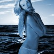 Angel girl in a sea at sunset time (toned in blue) — Foto de Stock
