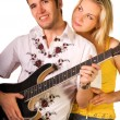 Young musician plays guitar and beautiful blond girl stands near - Stock Photo