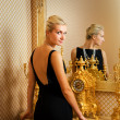Beautiful blonde girl near luxury the mirror — Stock Photo
