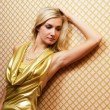 Beautiful blond girl in golden dress on abstract background — Stock Photo #4960327