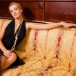 Sexy blond girl sitting on a luxury sofa — Stock Photo