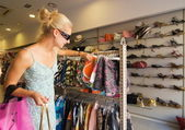 Blong girl buying clothes in a shop — Stock Photo