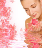 Beautiful girl with aroma bath ball in rendered water — Stock fotografie
