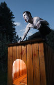 Scary man sitting on kennel and turning into werewolf — Stock Photo