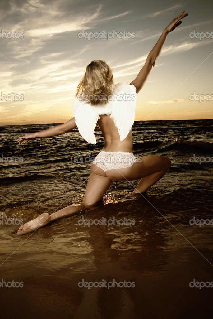 Beautiful angel in water at sunset (toned in sepia) — Stock Photo #4960090