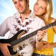 Young musician plays guitar and beautiful blond girl stands near — Stock Photo #5097798