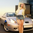 Sexy blond girl sits on modern sport car - Stok fotoğraf