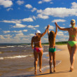 Mother and her two daughters walking on a beach — Stock Photo #5097864