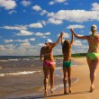 Mother and her two daughters walking on a beach - Stock Photo