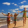 Mother and two daughters running on a beach near the water — Stockfoto #5097865
