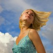 Beautiful blond girl and blue cloudy sky behind her — Stock Photo #5097893
