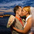 Just married couple kissing near the river at sunset time — Stock Photo