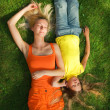 Two girls lying on a green grass - Photo