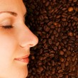Beautiful girl's face on over coffee bean background — Stock Photo