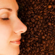 Beautiful girl&#039;s face on over coffee bean background - Stock Photo