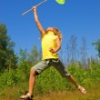 Стоковое фото: Young girl with butterfly net jumping on a meadow
